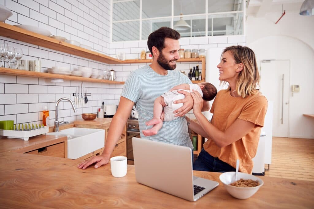 Busy Family In Kitchen At Breakfast With Father Caring For Baby Son